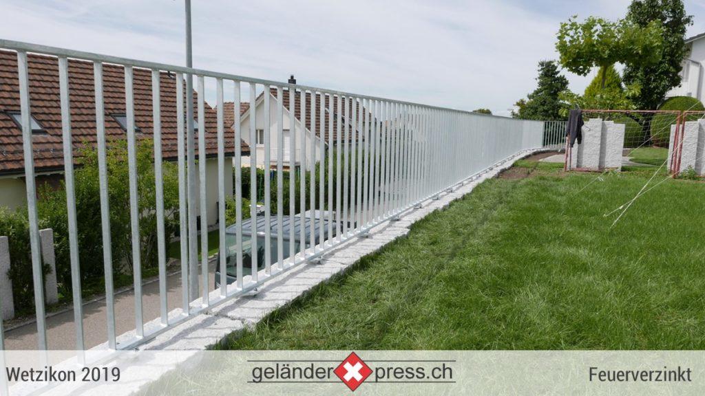 staketengelaender feuerverzinkt auf blocksteinmauer mit rasen